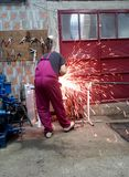 Man working with grinder. In garage causing lot of sparks royalty free stock photography