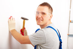 Man working with hammer. Smiling man working with hammer driving a nail in white wall in home, wearing protective clothes trousers, gloves and glasses. Part of Royalty Free Stock Images