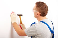 Man working with hammer. Driving a nail in white wall in home, wearing protective clothes trousers, gloves and glasses Royalty Free Stock Images