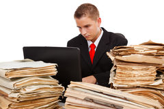 Man working hard. Man working on laptop computer, surrounded with lots of paperwork Royalty Free Stock Image