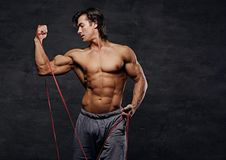 A man exercising with trx straps. A man working hard with fitness trx straps in a studio on grey background Stock Photos