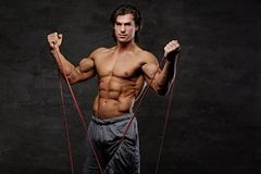 A man exercising with trx straps. A man working hard with fitness trx straps in a studio on grey background Royalty Free Stock Images