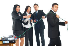 Man working hard and others do nothing. Three business people colleagues in a break drinking coffee , laughing out loud  and pointing to a businessman worker who Stock Image