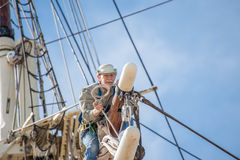 Man working at heights on a sailboat mast Royalty Free Stock Image
