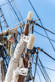 Man working at heights on a sailboat mast Stock Photos
