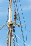 Man working at heights on a sailboat mast Stock Image