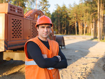 Man working in  helmet. Man working in   helmet on  background of the excavator Stock Images