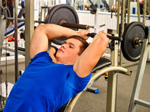 Man working his arms and chest at gym Stock Images