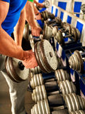 Man working his arms with dumbbells at gym Stock Photo