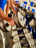 Man working his arms with dumbbells at gym Royalty Free Stock Image