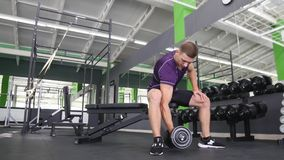 Man working his arms at the gym, He lifting the dumbbells and working his biceps.  Royalty Free Stock Photos