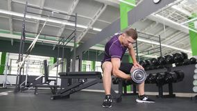Man working his arms at the gym, He lifting the dumbbells and working his biceps.  Royalty Free Stock Image