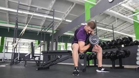 Man working his arms at the gym, He lifting the dumbbells and working his biceps.  Stock Photos
