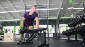 Man working his arms at the gym, He lifting the dumbbells and working his biceps. close up