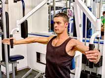 Man working his arms on training apparatus at gym Royalty Free Stock Image