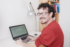Man working on his home studio. With glasses and red shirt Stock Image