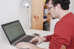 Man working on his home studio. With glasses and red shirt Stock Photo