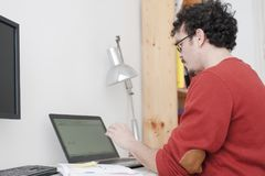 Man working on his home studio. With glasses and red shirt Royalty Free Stock Photography