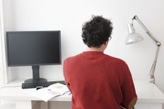 Man working on his home studio. With glasses and red shirt Royalty Free Stock Image