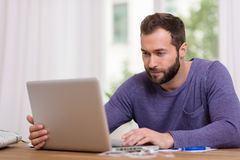 Man working on his laptop computer at home. Attractive bearded man in casual clothes sitting at a table working on his laptop computer at home in front of a Royalty Free Stock Image
