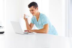 Man working on his laptop , drinking coffee in the kitchen Royalty Free Stock Image
