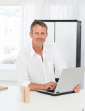 Man working on his laptop in his kitchen Royalty Free Stock Photo