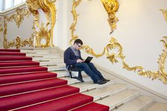 A man working at his laptop on the main staircase of the winter Palace. The Hermitage.Unconventional workplaces Royalty Free Stock Image