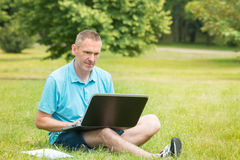 Man working on his laptop in the park. Man sitting on grass in the park and working on his laptop Stock Images