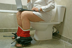 Man working with his laptop in WC. Man sitting on toilet bowl with a laptop Royalty Free Stock Photos