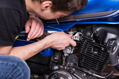 Man Working on his Motorbike Using Wrench Tool Royalty Free Stock Image