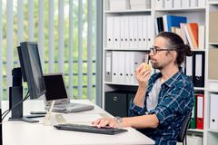 Man is working in his officeand eating apple. Creative man is working in his office and eating apple Stock Photo