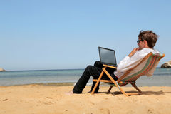Man working at his pc at the beach Royalty Free Stock Images