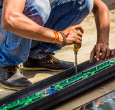 A man working with his screwdriver tool Stock Image