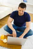 Man working at home. Casual young man working at home on his laptop computer, sitting on floor, looking at screen. High angle view Royalty Free Stock Photos