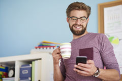 Man working at home. Man browsing mobilephone and drinking coffee Royalty Free Stock Images