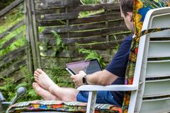Man working from home in the garden using smart phone and notebook computer Stock Images