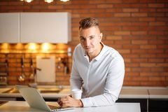 Entrepreneur sitting in his office holding cup of coffee smiling to camera. Man working at home with laptop on the kitchen desk, holding cup of coffee and Royalty Free Stock Photo