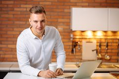 Entrepreneur sitting in his office holding cup of coffee smiling to camera. Man working at home with laptop on the kitchen desk, holding cup of coffee and Royalty Free Stock Photos