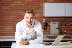 Entrepreneur sitting in his office holding cup of coffee smiling to camera. Man working at home with laptop on the kitchen desk, holding cup of coffee and Royalty Free Stock Image