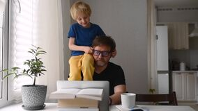 Man working from home with laptop during quarantine. Home office and parenthood at same time. Exhausted parent with hyperactive ch