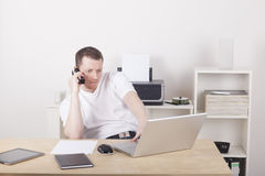 Man working in home office. Young man working in a office, using a laptop computer and having a phone call Royalty Free Stock Image