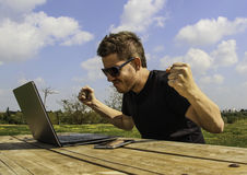 A man with laptop - Sitting in the garden, with arms up Royalty Free Stock Image