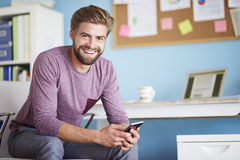 Man working at home. Smiling a lot while using mobilephone Royalty Free Stock Images