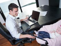 Man working from home and take care of baby Stock Photography