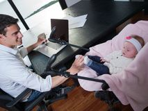 Man working from home and take care of baby Stock Images