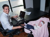 Man working from home and take care of baby Stock Image