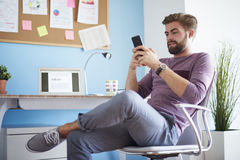 Man working at home. Man texting with his mobilephone Royalty Free Stock Photography