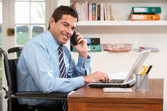 Man Working From Home Using Laptop On Phone Royalty Free Stock Image