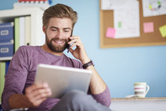 Man working at home. Using mobilephone and digital tablet Stock Photography