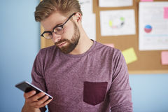Man working at home. Young man browsing his mobilephone Stock Images
